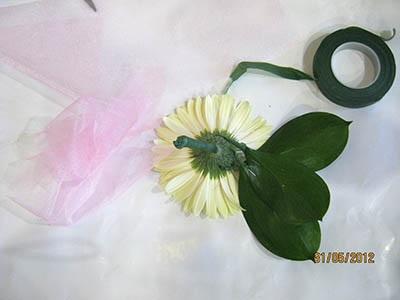 На проволоку кладем зафиксированные степлером листья рускуса и закрепляем их тейп лентой