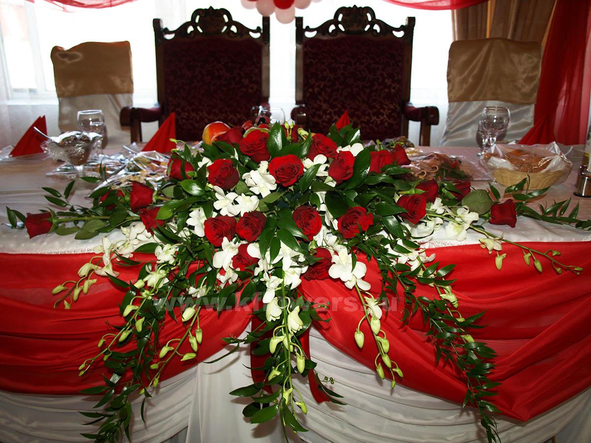 Композиция на стол молодых: розы, орхидеи дендробиум, итальянский рускус