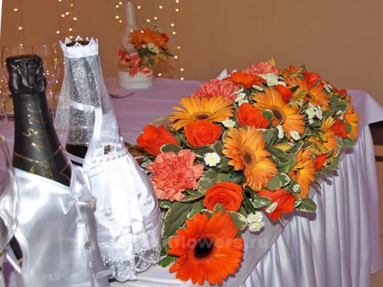 Оригинально оформленное свадебное шампанское рядом с живыми цветами