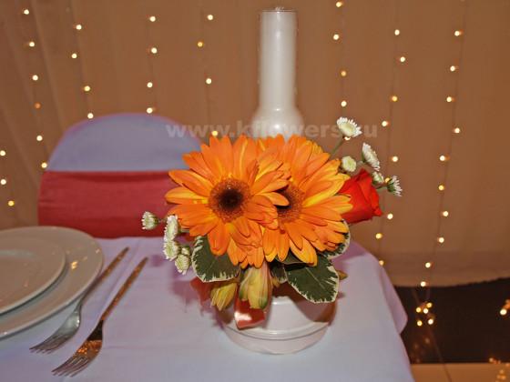 Цветочная миниатюра со свечей на столе новобрачных