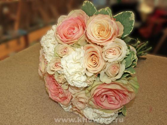 Круглый букет невесты выполнен в нежных пастельных тонах, выбранных для свадебного декора