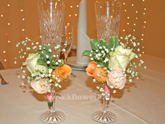 Очаровательные цветочные миниатюры прикреплены к ножкам бокалов ленточками